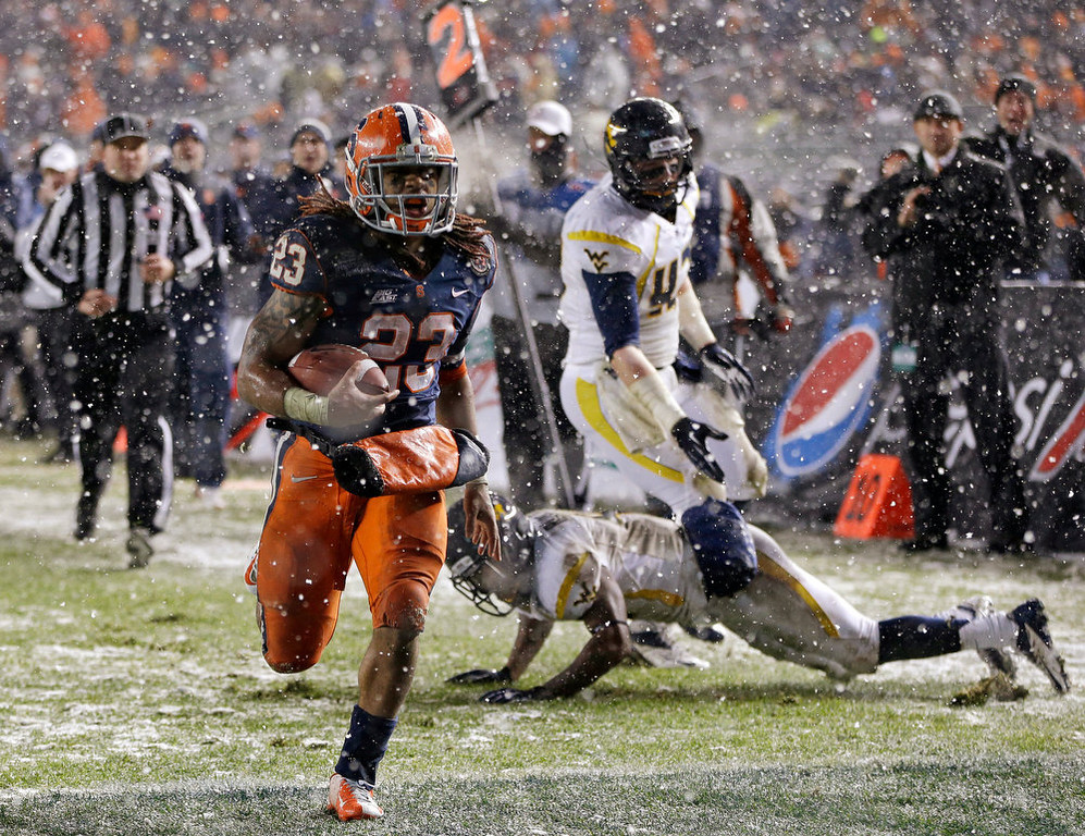Description of . Syracuse running back Prince-Tyson Gulley (23) scores a touchdown, leaving West Virginia defenders in his wake during the third quarter of the Pinstripe Bowl NCAA college football game at Yankee Stadium in New York, Saturday, Dec. 29, 2012. Syracuse won 38-14. (AP Photo/Kathy Willens)