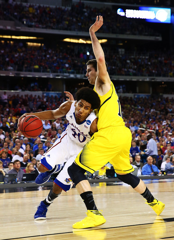 Description of . ARLINGTON, TX - MARCH 29:  Kevin Young #40 of the Kansas Jayhawks drives against Glenn Robinson III #1 of the Michigan Wolverines in the first half during the South Regional Semifinal round of the 2013 NCAA Men\'s Basketball Tournament at Dallas Cowboys Stadium on March 29, 2013 in Arlington, Texas.  (Photo by Tom Pennington/Getty Images)