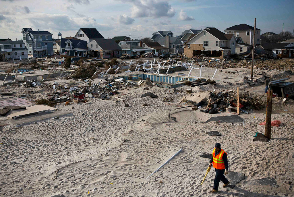 Description of . A man walks amongst properties damaged by Hurricane Sandy in the Ortley Beach area of Toms River, New Jersey November 28, 2012. The storm made landfall along the New Jersey coastline on October 29. REUTERS/Andrew Burton