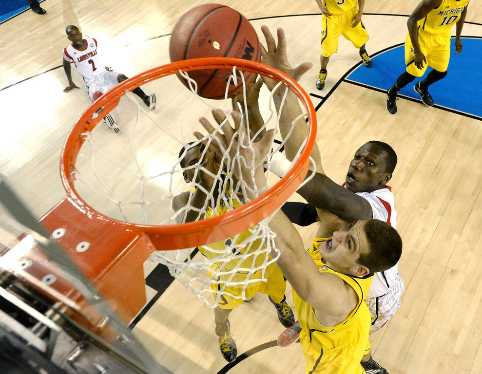 Description of . Michigan Wolverines forward Glenn Robinson III (lower) reaches for a rebound against Louisville Cardinals center Gorgui Dieng (top) in the first half of their NCAA men's Final Four championship basketball game in Atlanta, Georgia April 8, 2013. REUTERS/Chris Steppig-Pool