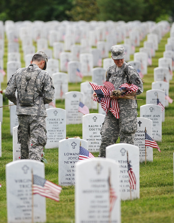 Description of . Members of the Third US Infantry Regiment, The Old Guard, place flags in front of graves at Arlington National Cemetery on May 23, 2013 in Arlington, Virginia ahead of Memorial Day.  AFP PHOTO/Mandel NGAN/AFP/Getty Images