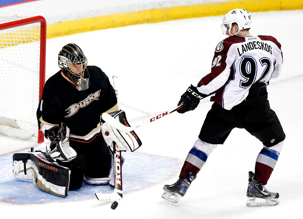 Description of . Anaheim Ducks goalie Jonas Hiller, left, blocks a shot by Colorado Avalanche left wing Gabriel Landeskog during overtime of an NHL hockey game in Anaheim, Calif., Sunday, Feb. 24, 2013. The Ducks won 4-3. (AP Photo/Chris Carlson)