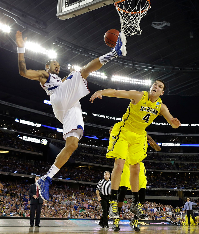 Description of . Kansas\' Travis Releford is fouled by Michigan\'s Mitch McGary (4) during the second half of a regional semifinal game in the NCAA college basketball tournament, Friday, March 29, 2013, in Arlington, Texas. (AP Photo/Tony Gutierrez)