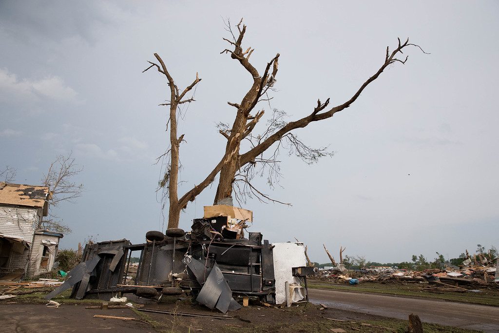 Description of . A camper trailer is wrapped around a tree in Pilger, Neb.,  following a tornado on Monday, June 16, 2014.  The National Weather Service says the storm that struck northeast Nebraska appears to have produced four tornadoes, one of which ravaged the town of Pilger.   (AP Photo/The World-Herald, Ryan Soderlin)