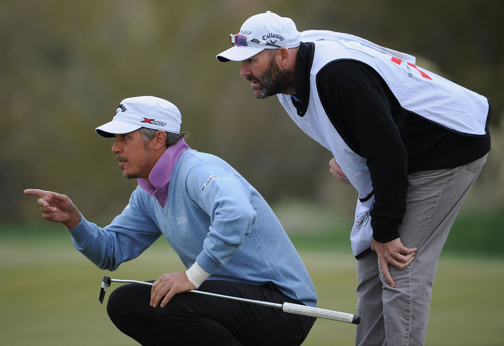 Description of . MARANA, AZ - FEBRUARY 21:  Fredrik Jacobson and caddie Neil Wallace line up a putt on the 18th hole during the first round of the World Golf Championships - Accenture Match Play at the Golf Club at Dove Mountain on February 21, 2013 in Marana, Arizona. Round one play was suspended on February 20 due to inclimate weather and is scheduled to be continued today.  (Photo by Stuart Franklin/Getty Images)
