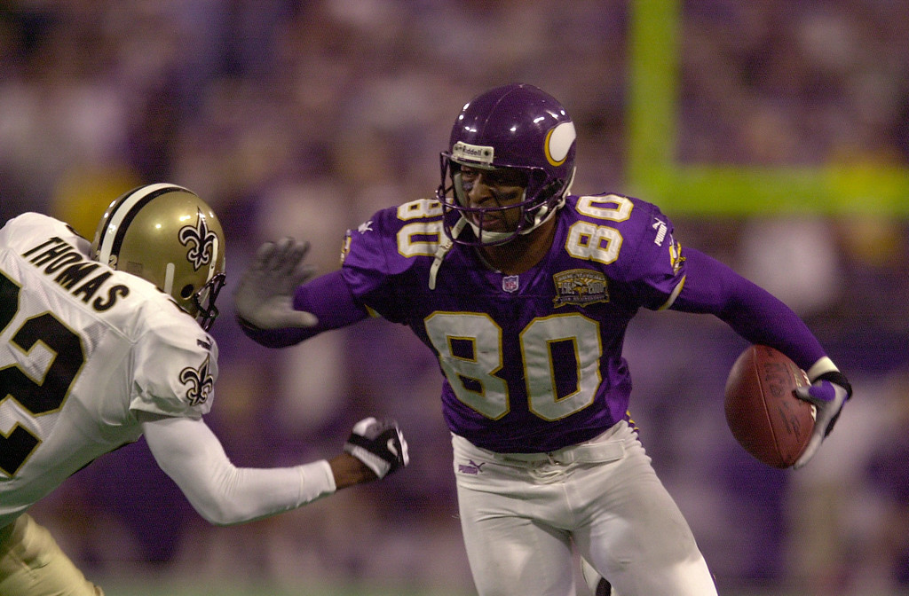 Description of . 6 Jan 2001: Cris Carter #80 of the Minnesota Vikings gets past Fred Thomas #22 of the New Orleans Saints for the first down at the Hubert H. Humphrey Metrodome in Minneapolis, Minnesota. The Minnesota Vikings beat the New Orleans Saints 34-16.  Mandatory Credit: Elsa/ALLSPORT