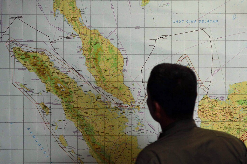 Description of . A member of the Indonesian Air Force at Medan city military base inspects the Indonesian military search operation for the missing Malaysian Airlines flight MH370 on March 12, 2014 in the area of Malacca Strait, a sea passageway between Indonesia (seen left of the map) and Malaysia (seen top left of the map). Malaysia faced a storm of criticism on March 12 over contradictions and information gaps in the hunt for a missing airliner with 239 people on board, as the search zone dramatically veered far from the intended flight path.       AFP PHOTO / ATARATAR/AFP/Getty Images