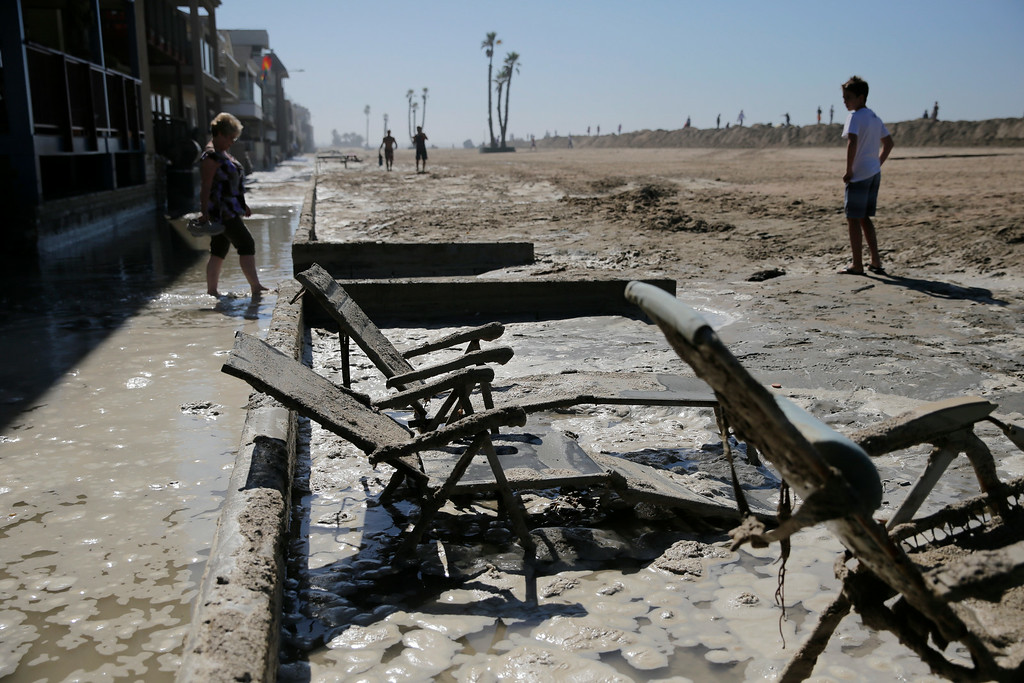 Description of . Beach chairs are covered in mud in the flooded beachfront area on Wednesday, Aug. 27, 2014, in Seal Beach, Calif. (AP Photo/Jae C. Hong)