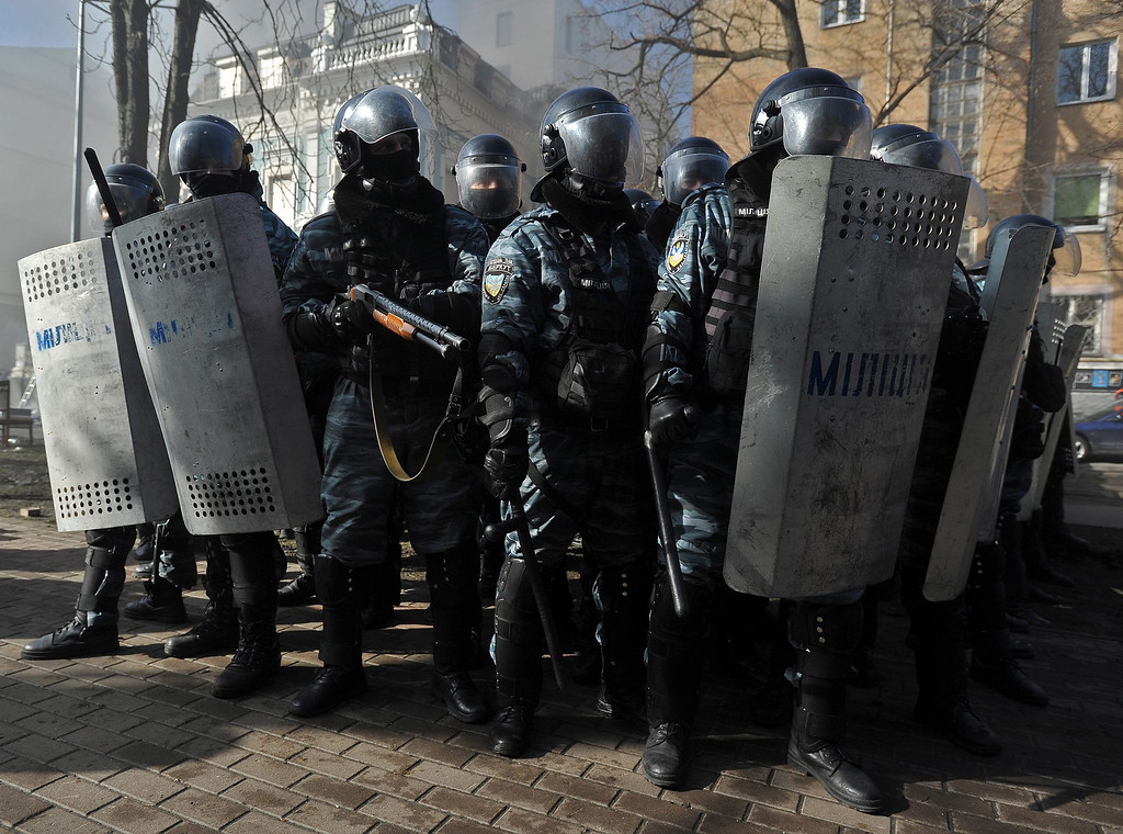 Description of . Riot policemen stand during an anti-government protest in downtown Kiev, Ukraine, 18 February 2014. A least three protesters were killed in clashes with police on 18 February, Ukrainian opposition activists say.  EPA/ALEXEY FURMAN
