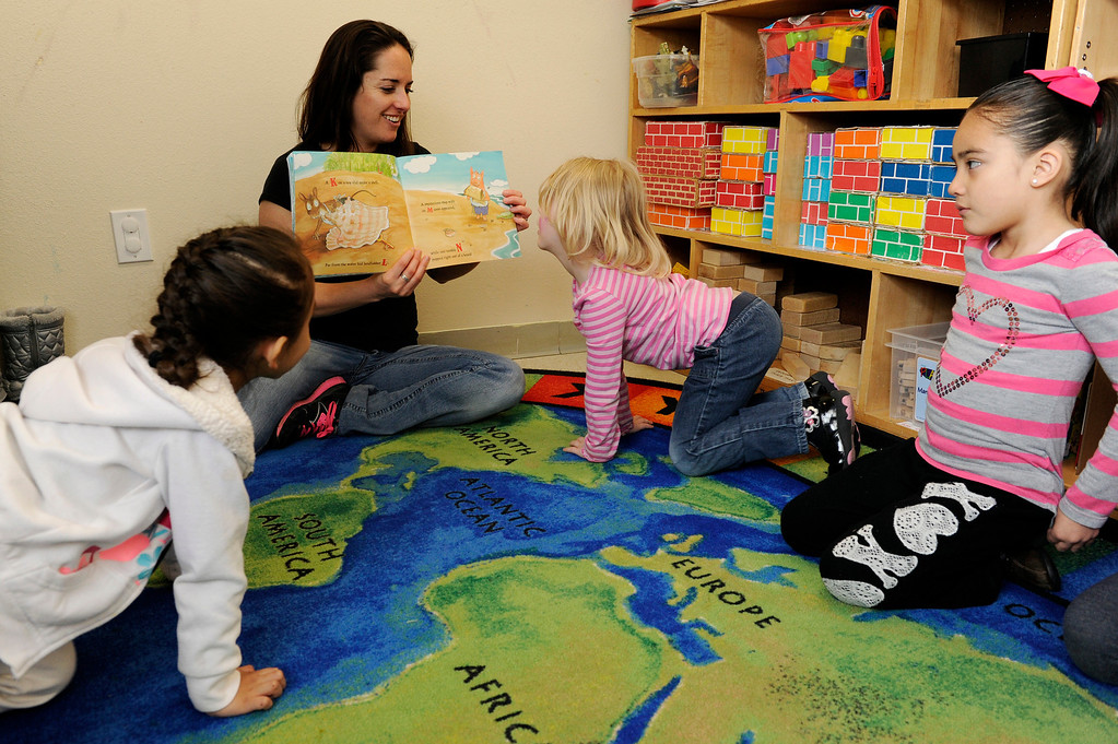 Description of . DENVER, CO - APRIL 3: Kate Murphy, a teacher at the Children's Outreach Project, reads a book about letters to (from left) Sophia S., 4, Æstra R., 4, and Heidy P., 5, during class on April 3, 2014, in Denver, Colorado. The school is a nonprofit that provides therapy, education and daycare to children between 2-6 years old who have developmental delays like moderate Down syndrome and speech impediments. (Photo by Anya Semenoff/The Denver Post)