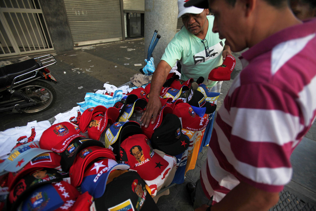 Description of . A street vendor sells baseball caps decorated with images of Venezuela's late President Hugo Chavez, and T-shirts with a the words in Spanish
