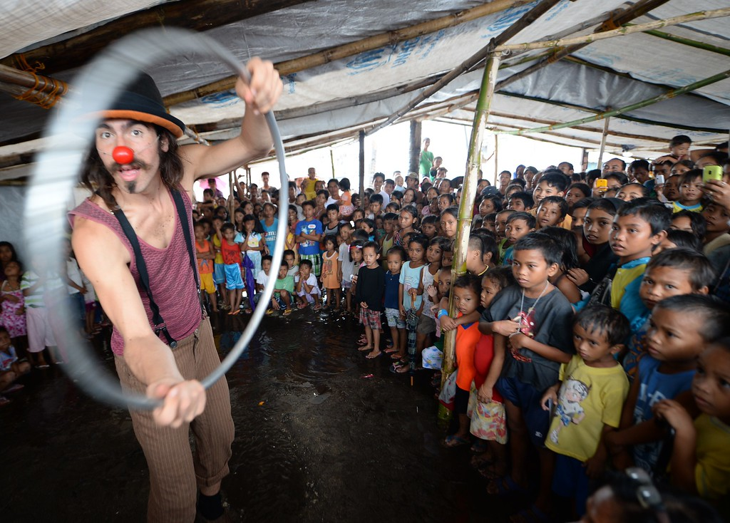 Description of . A member of Clowns Without Borders performs in front of young survivors of the super Typhoon Haiyan as part of recovery work by Plan international at a tent city in Tacloban city, Leyte province, on December 25, 2013.  Survivors of the Philippines' deadliest typhoon spent a gloomy Christmas Day surrounded by mud December 25 as heavy rain drove many inside their flimsy shelters, dampening efforts to retain some holiday cheer in the deeply devout nation.    AFP PHOTO/TED ALJIBETED ALJIBE/AFP/Getty Images