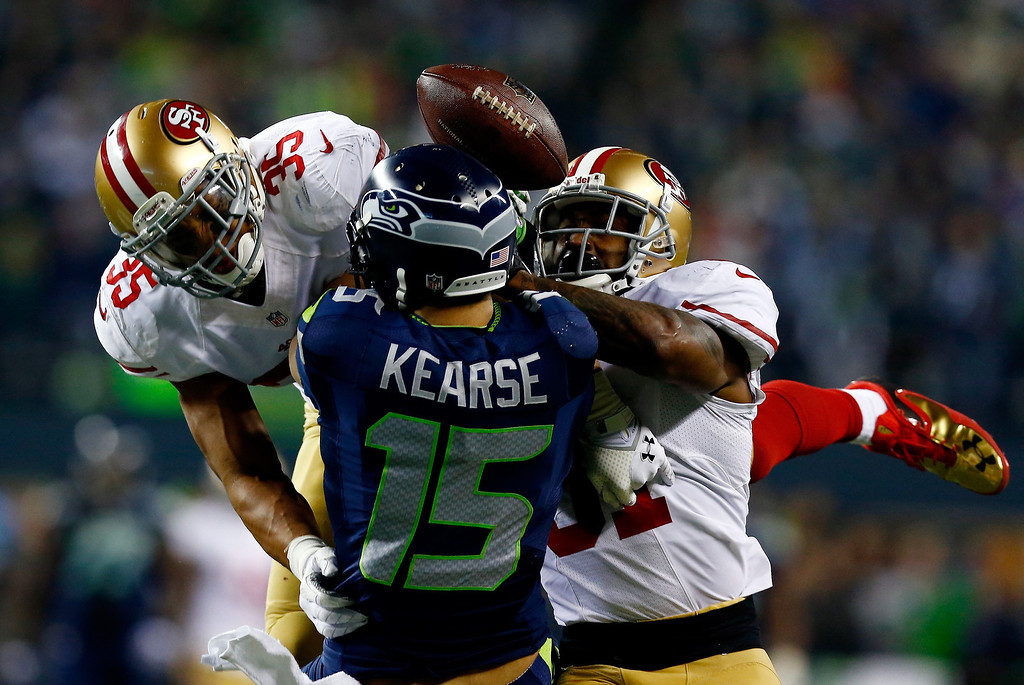 . Wide receiver Jermaine Kearse #15 of the Seattle Seahawks is hit by free safety Eric Reid #35 and strong safety Donte Whitner #31 of the San Francisco 49ers to break up the pass in the second half in the 2014 NFC Championship at CenturyLink Field on January 19, 2014 in Seattle, Washington.  (Photo by Tom Pennington/Getty Images)
