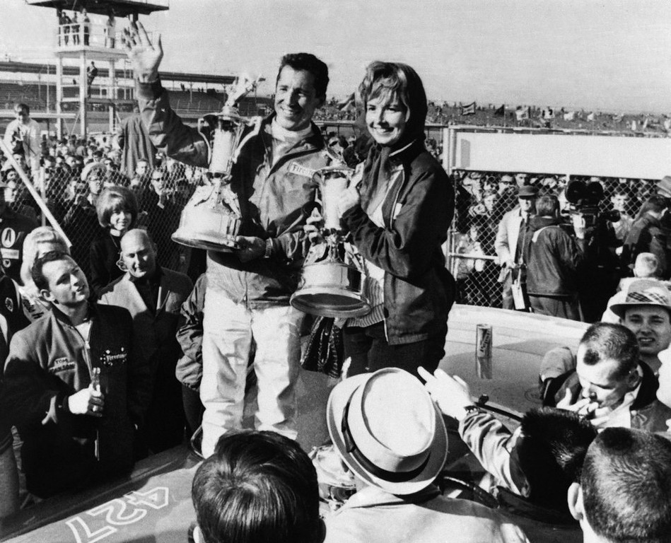 Description of . Mario Andretti of Nazareth, Pa., holds up his trophy with his wife by his side after he won the Daytona 500-Mile Stock Race on Feb. 26, 1967 at Daytona Beach, Florida. He finished the 200-lap race driving a 1967 ford. (AP Photo)