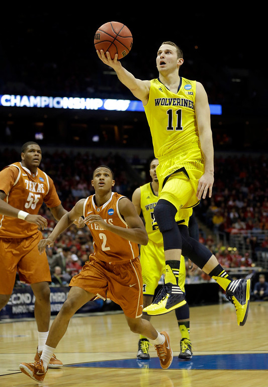 Description of . Michigan guard Nik Stauskas (11) drives to the basket during the first half of a third-round game against the Texas of the NCAA college basketball tournament Saturday, March 22, 2014, in Milwaukee. (AP Photo/Morry Gash)