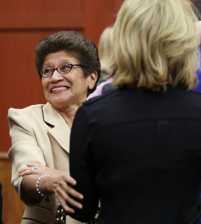 Description of . George Zimmerman's family, including Gladys Zimmerman, center, celebrate following George Zimmerman's not guilty verdict in Seminole Circuit Court in Sanford, Fla. on Saturday, July 13, 2013. Jurors found Zimmerman not guilty of second-degree murder in the fatal shooting of 17-year-old Trayvon Martin in Sanford, Fla. The six-member, all-woman jury deliberated for more than 15 hours over two days before reaching their decision Saturday night. (AP Photo/Gary W. Green, Pool)