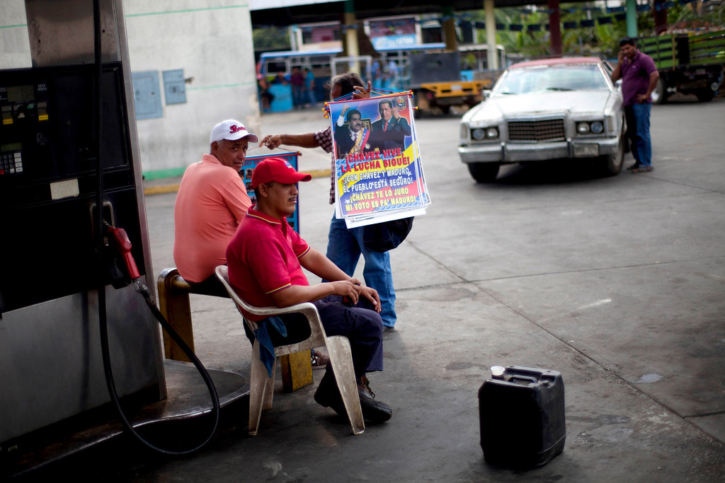 Description of . In this April 8, 2013 photo, street vendor Jose Gonzalez, 62, tries to persuade gas stations workers to buy some posters featuring Venezuela's late President Hugo Chavez and acting President Nicolas Maduro, in Tacarigua, Venezuela. Outside Venezuela's capital, power outages, food shortages and unfinished projects abound; important factors heading into Sunday's election to replace Chavez, who died last month after a long battle with cancer.  Polls show that support for Maduro, Chavez's hand-picked successor, may be eroding and constant power outages are a testament to the neglect many Venezuelans consider inexcusable in this major oil-producing state. (AP Photo/Ramon Espinosa)