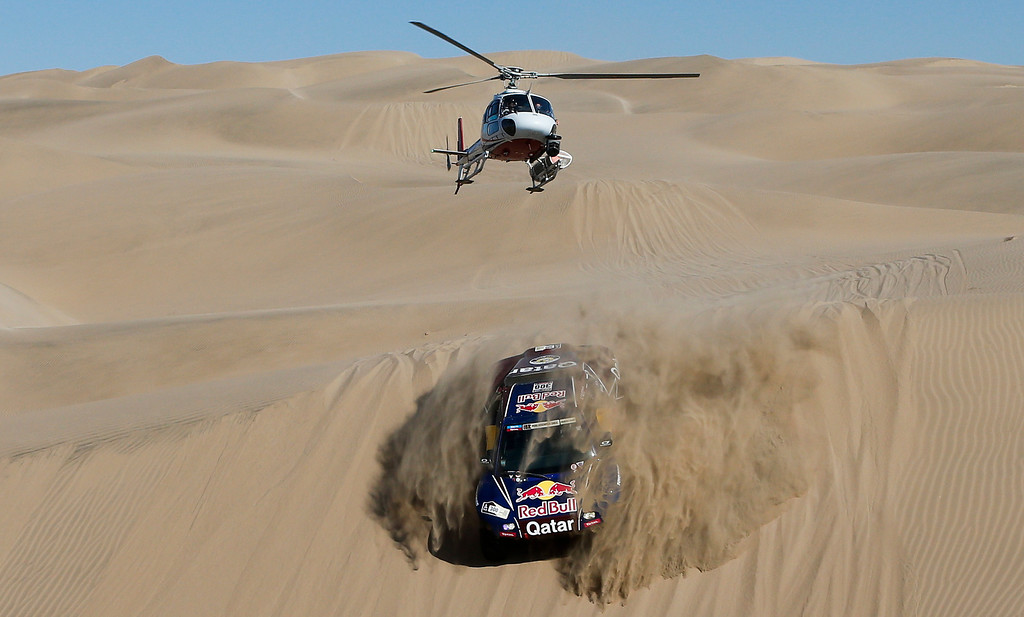 Description of . A helicopter flies over driver Nasser Al-Attiyah of Qatar and co-driver Lucas Cruz of Spain competing in the 4nd stage of the 2013 Dakar Rally from Nazca to Arequipa, Peru,  Tuesday, Jan. 8, 2013. The race finishes in Santiago, Chile, on Jan. 20. (AP Photo/Victor R. Caivano)