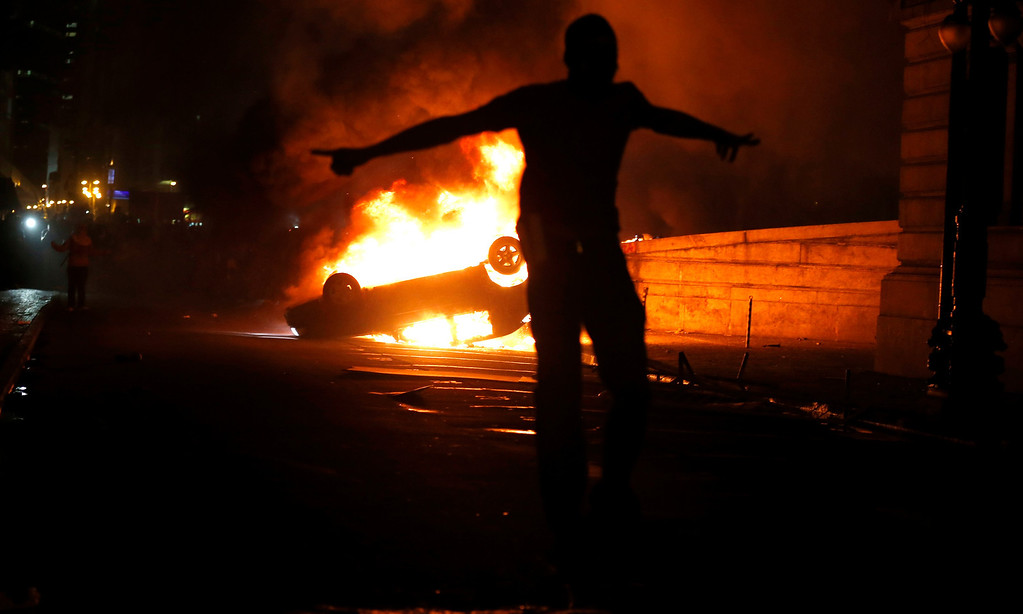 Description of . A demonstrator celebrates by a burning car in downtown Rio de Janeiro June 17, 2013. Tens of thousands of demonstrators marched through the streets of Brazil's biggest cities on Monday in a growing protest that is tapping into widespread anger at poor public services, police violence and government corruption.  REUTERS/Sergio Moraes
