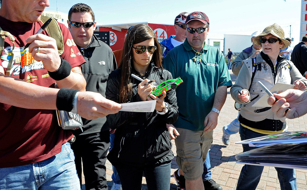 . NASCAR Sprint Cup Series driver Danica Patrick (C), of the number 10 car, signs autographs for fans as she walks toward the garage area during practice for the Daytona 500 at Daytona International Speedway in Daytona Beach, Florida, February 20, 2013. REUTERS/Brian Blanco