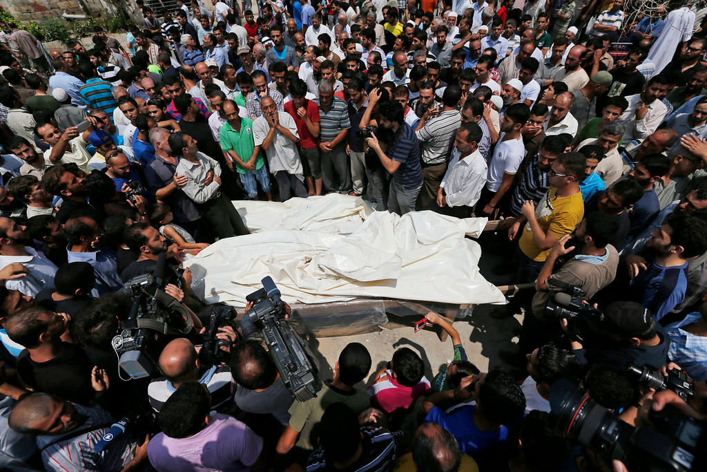 Description of . Mourners gather around the bodies of seven members of the Kelani family, killed overnight by an Israeli strike in Gaza City, during their funeral in Beit Lahiya, northern Gaza Strip, on Tuesday, July 22, 2014. Ibrahim Kelani, 53, his wife Taghreed and their five children, were killed in the strike on a Gaza City high-rise. Ibrahim's brother Saleh Kelani said Tuesday that his brother and his brotherís children, ranging in age from four to 12, had German citizenship, while his wife had not. The family had rented the apartment in the high-rise after fleeing their home in the northern Gaza town of Beit Lahiya which came under heavy shelling by the Israeli army. (AP Photo/Lefteris Pitarakis)