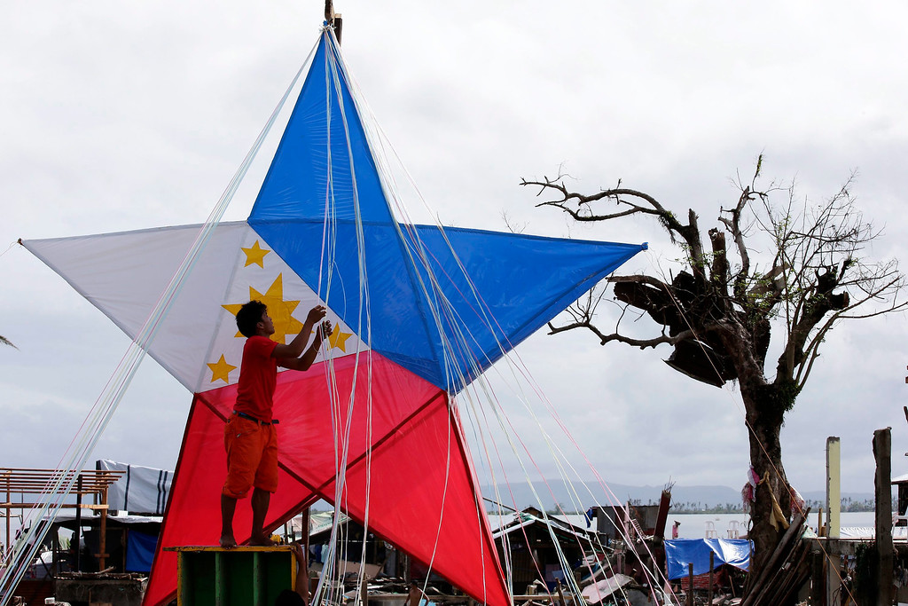 Description of . A Filipino typhoon victims prepares a giant Christmas lantern in the typhoon devastated city of Tacloban, Leyte Province, Philippines, 24 December 2013. Town officials have launched a contest for the best Christmas decoration among the villages in the city of Tacloban, with a first prize of some 1694 euros. The destruction and losses in lives and properties caused by Haiyan are casting a pall over the holiday season, in a country known for having the world's longest celebration of Christmas. According to the Philippine disaster relief agency, 6,102 people were killed and 1,779 were still missing from Haiyan's onslaught. The typhoon, the world's strongest on record, destroyed more than 1 million homes, key infrastructure and commercial establishments.  EPA/DENNIS M. SABANGAN