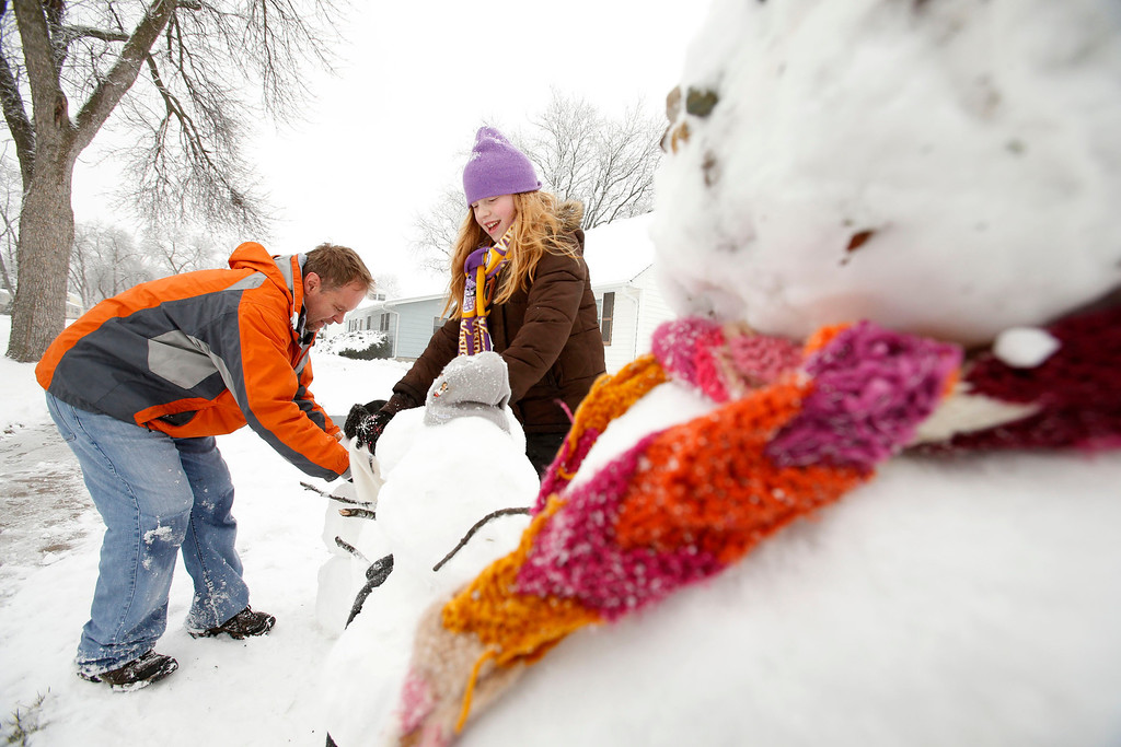 Description of . Eleven-year-old Quinn Dzikonski and her father Craig Dzikonski build a family of snowmen outside their home in Cedar Rapids, Iowa on Thursday, December 20, 2012. The first widespread snowstorm of the season crawled across the Midwest on Thursday, with whiteout conditions stranding holiday travelers and sending drivers sliding over slick roads _ including into a fatal 25-vehicle pileup in Iowa. †(AP Photo/The Gazette-Cliff Jette)