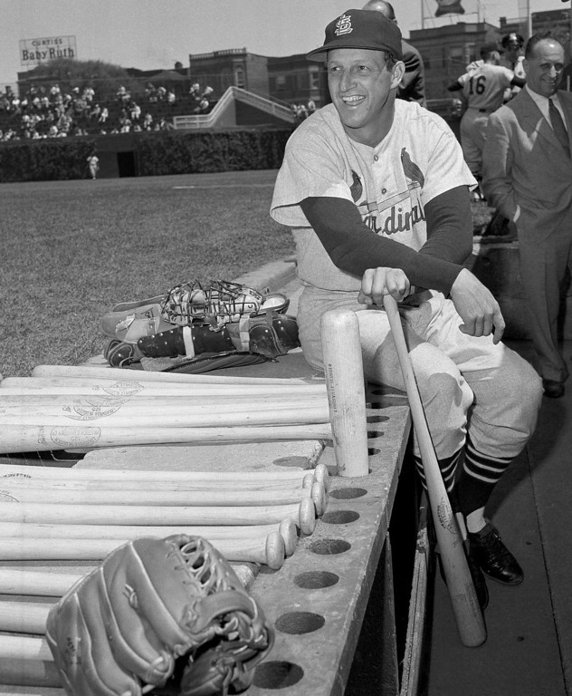 Description of . FILE - In this May 13, 1958 file photo, Stan Musial, St. Louis Cardinal all-time great baseball player, poses in dugout prior a baseball game against the Chicago Cubs in Chicago. Musial made his 3,000th career hit in the game. Musial, one of baseball's greatest hitters and a Hall of Famer with the Cardinals for more than two decades, died Saturday, Jan. 19, 2013, the team announced. He was 92. (AP Photo/File)