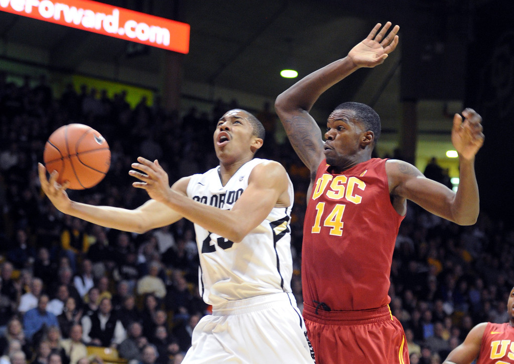 Description of . Spencer Dinwiddie of Colorado drives past DeWayne Dedmon of Southern California during the first half of the January 10, 2013 game in Boulder.  Cliff Grassmick / Daily Camera