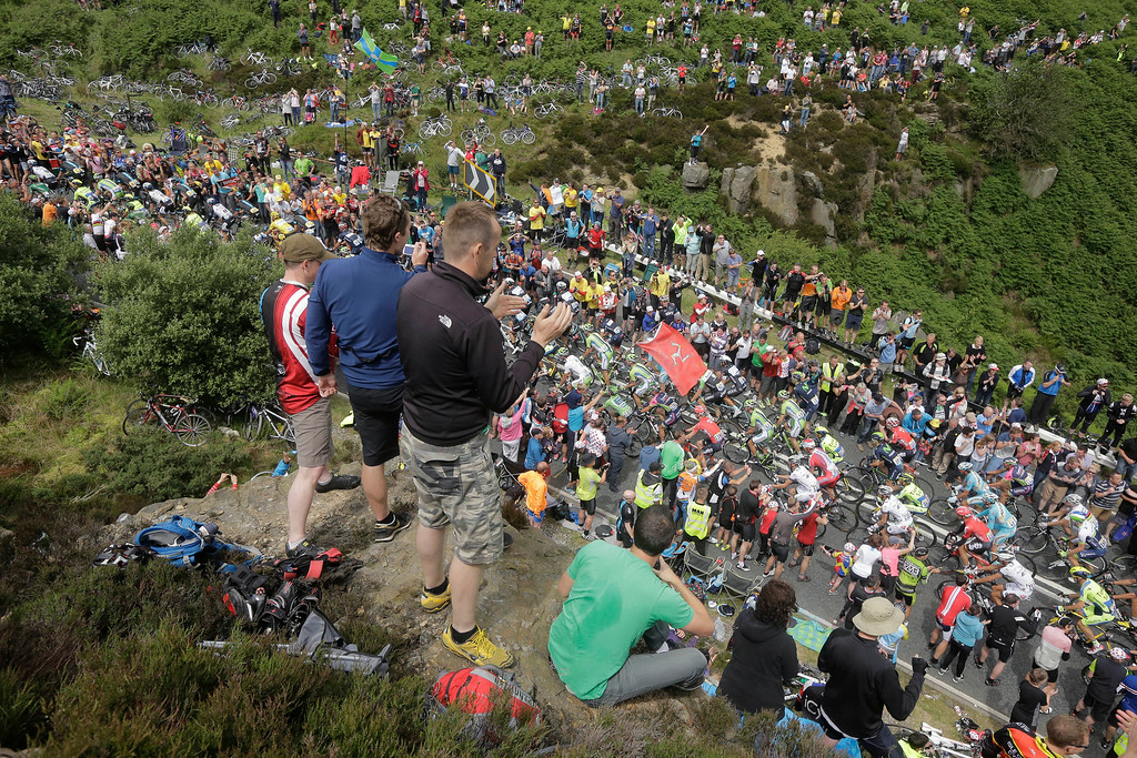 Description of . Spectators line the road as the pack climbs Blubberhouses pass during the second stage of the Tour de France cycling race over 201 kilometers (124.9 miles) with start in York and finish in Sheffield, England, Sunday, July 6, 2014. (AP Photo/Laurent Cipriani)