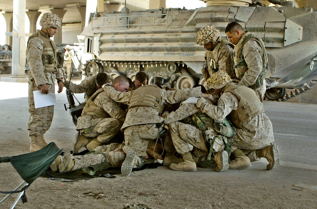 . U.S. Marines pray over a fallen comrade at a first aid point after he died from wounds suffered in fighting in Fallujah, Iraq, Thursday, April 8, 2004. Hundreds of U.S. Marines had been fighting insurgents in several neighborhoods in the western Iraqi city of Fallujah in order to regain control of the city. (AP Photo/Murad Sezer)