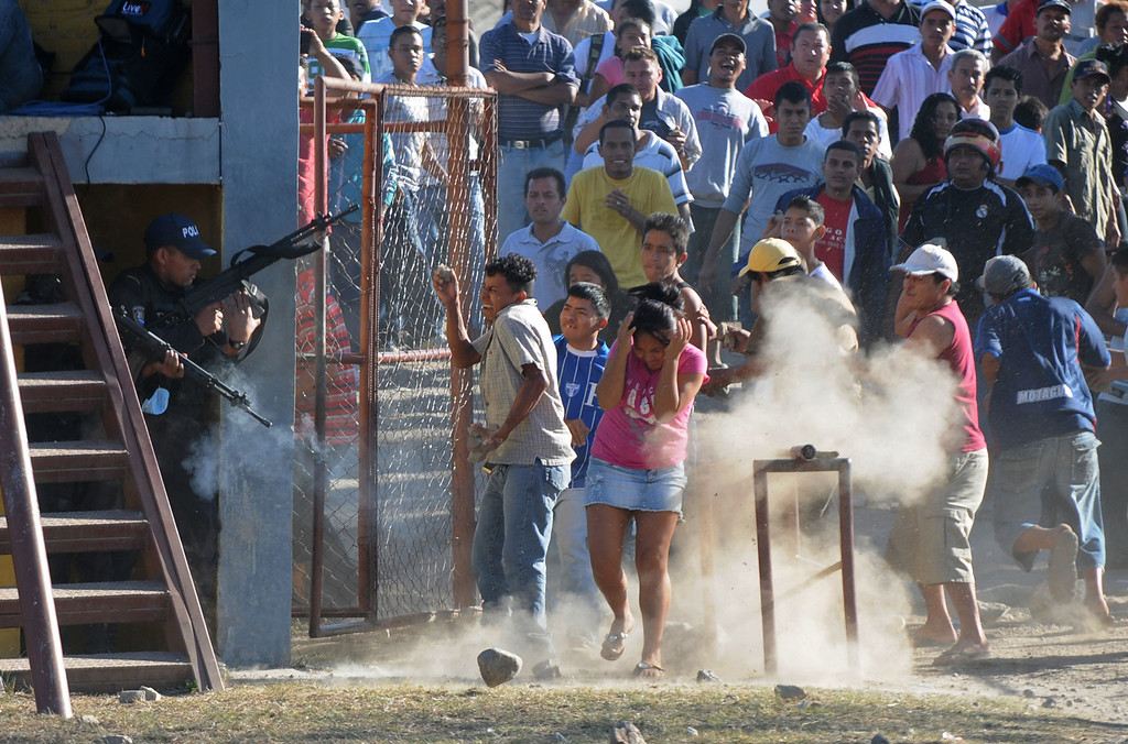 Description of . In this Feb. 15, 2012 file photo, inmates relatives clash with police outside a prison after a deadly fire in Comayagua, Honduras.  Over 300 inmates perished in the fire that swept through the prison north of Tegucigalpa. More than half the inmates were still awaiting trial.  Many of those who died had been locked up for petty crimes: stealing a wallet, robbing a truck. Some had never been charged. (AP Photo/Fernando Antonio, File)