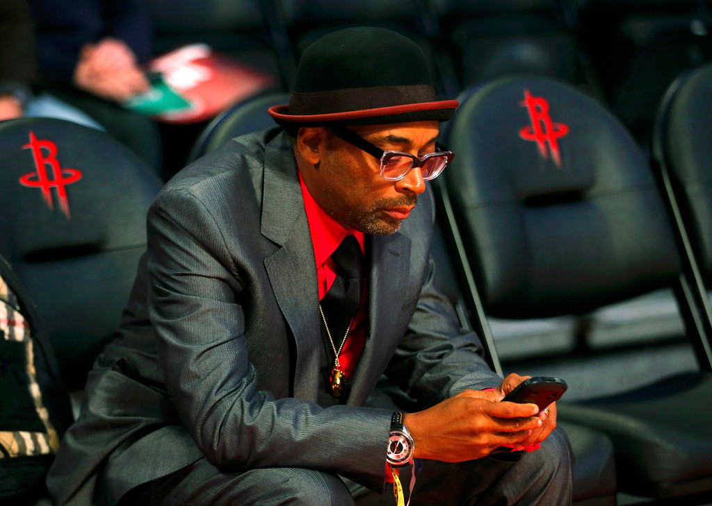 Description of . Film director Spike Lee looks at his phone before the All Star slam dunk competition during the NBA basketball All-Star weekend in Houston, Texas, February 16, 2013. REUTERS/Jeff Haynes