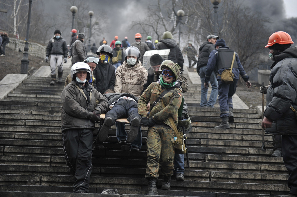 Description of . Protesters carry a wounded demonstrator in Kiev on February 20, 2014. Hundreds of armed protesters charged police barricades Thursday on Kiev's central Independence Square, despite a truce called just hours earlier by the country's embattled president.  AFP PHOTO / LOUISA GOULIAMAKI/AFP/Getty Images