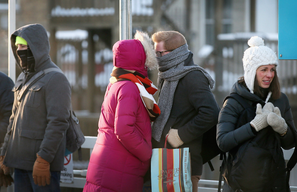 ". Passengers heading into downtown share some warmth as while they wait on an ""L\"" platform for the train to arrive in below zero temperatures on January 7, 2014 in Chicago, Illinois. Platforms were crowded and trains were delayed because doors on the trains kept freezing open. Chicago is experiencing its third consecutive day of below-zero temperatures.  (Photo by Scott Olson/Getty Images)"