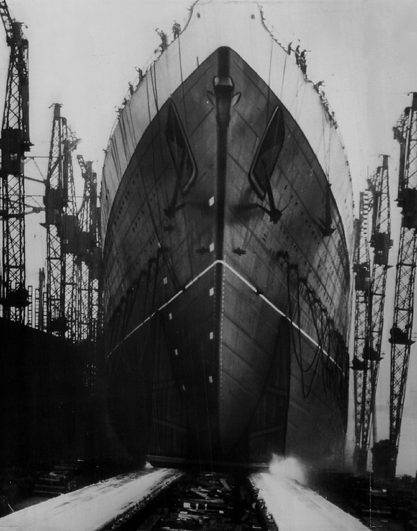 Description of . Sliding Down the Ways at Clydebank, Scotland, the new queen of the seas, the Queen Elizabeth, largest liner in the world, is shown here being launched on Oct. 4 ,1938. King George had intended to be present, but the European crisis kept him in London. The Queen Elizabeth, 1,030 feet long and with a gross tonnage of 85,000, took to the water without a hitch.