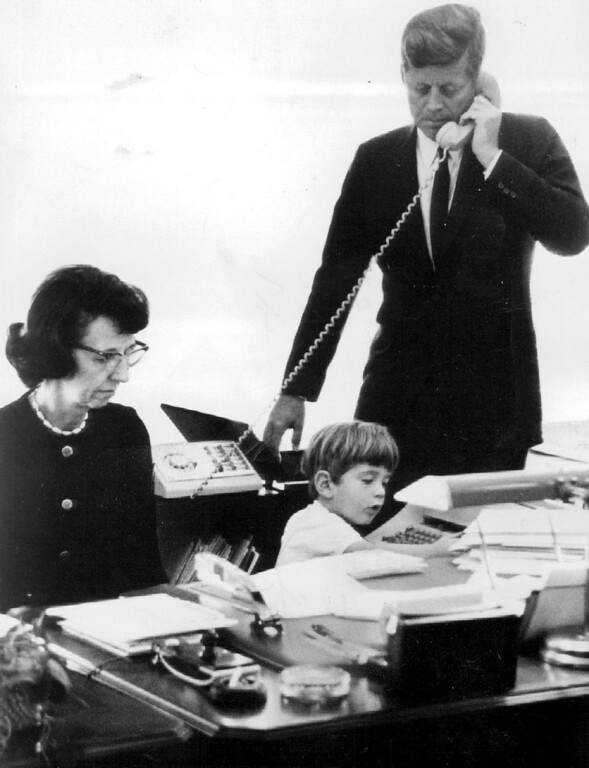 Description of . Secretary Evelyn Lincoln works in the President's office with Kennedy as John Jr. busies himself in 1963. Denver Post file