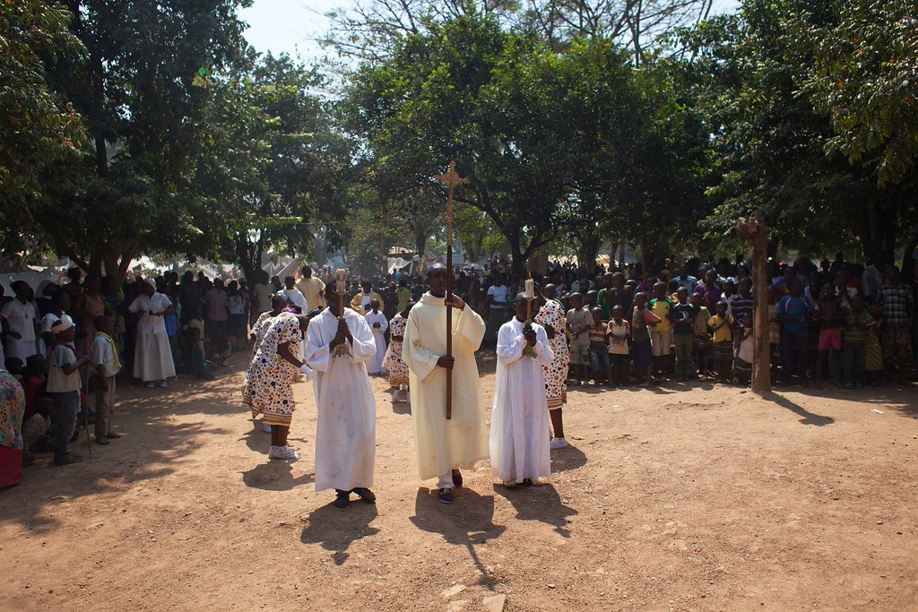 Description of . Catholic priests lead a special Christmas Day mass for children, in a monastery ground serving as a camp for the displaced, in Bangui, Central African Republic, Wednesday, Dec. 25, 2013. According to the United Nations High Commissioner for Refugees, more than 200,000 people remain displaced in the capital alone, and more than half of those are children. Many of the displaced lack even basic shelter from the elements, while hunger is rampant and insecurity growing in the overcrowded and rudimentary camps. (AP Photo/Rebecca Blackwell)