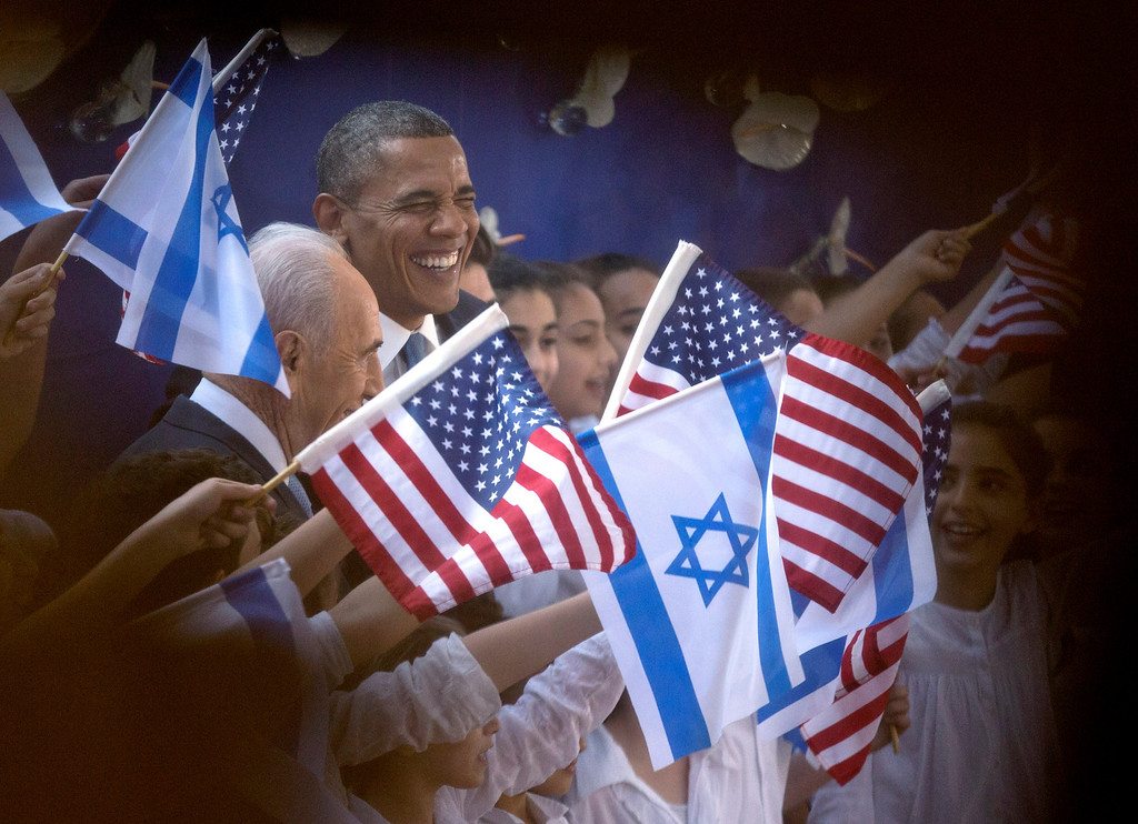Description of . President Barack Obama and Israeli President Shimon Peres, left, are photographed through a window and the crowd as they are greeted by children waving Israeli and American flags upon their arrival at the Peres' residence, Wednesday, March 20, 2013, in Jerusalem. (AP Photo/Carolyn Kaster)