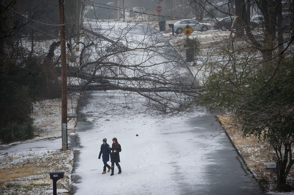 Description of . Emmanuel Jones, left, and mom Kelly Jones walk back to their house after surveying their neighborhood during a winter storm that brought down trees and power lines leaving them without power on Wednesday, Feb. 12, 2014, in Doraville, Ga. (AP Photo/John Amis)