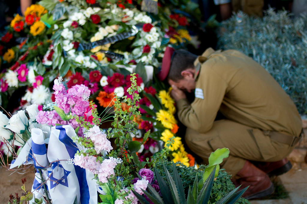 Description of . An Israeli soldier of the Maglan elite unit morns over the grave of Staff Sgt. Matan Gotlib, a Maglan elite unit soldier, during his funeral in the military cemetery in Rishon Letzion, central Israel, Thursday, July 31, 2014. Gotlib, 21, was killed in combat on Wednesday in the southern Gaza Strip. (AP Photo/Ariel Schalit)