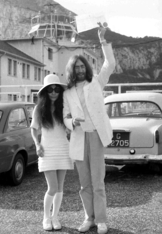 Description of . Beatle John Lennon waves his marriage certificate as his bride, Japanese artist Yoko Ono, stands at his side after their wedding at the Rock of Gibraltar on March 20, 1969. They are about to board a chartered jet to Paris where they will honeymoon. (AP Photo)