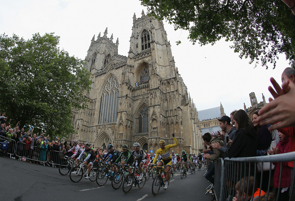 Description of . YORK, ENGLAND - JULY 06:  The peloton leaves the start of stage two of the 2014 Le Tour de France from York to Sheffield on July 6, 2014 in York, United Kingdom.  (Photo by Doug Pensinger/Getty Images)