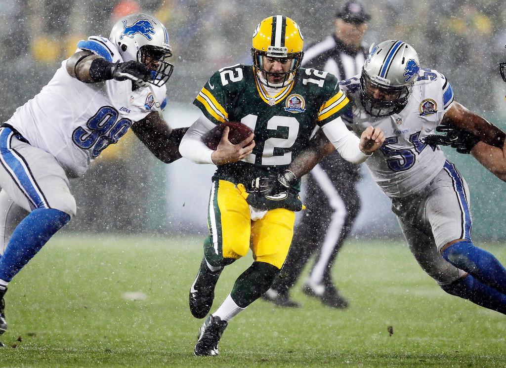 Description of . Green Bay Packers quarterback Aaron Rodgers (12) tries to run between Detroit Lions' Nick Fairley (98) and DeAndre Levy (54) during the first half of an NFL football game Sunday, Dec. 9, 2012, in Green Bay, Wis. (AP Photo/Mike Roemer)