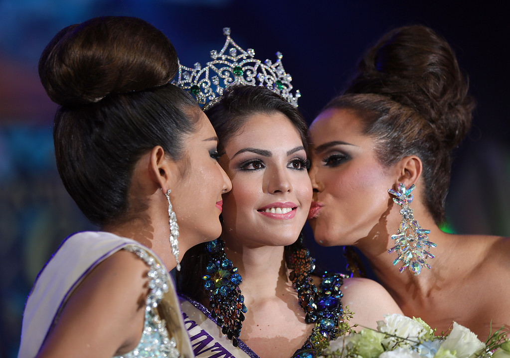 Description of . Marceki Ohio of Brazil, center, is congratulated by the two runners-up from Thailand Nethnapada Kanrayanon, left, and Shantell D'Marco of the US, right, after winning the crown at the Miss International Queen 2013 transgender beauty pageant in Pattaya, southeastern Thailand Friday, Nov. 1, 2013. (AP Photo/Apichart Weerawong)