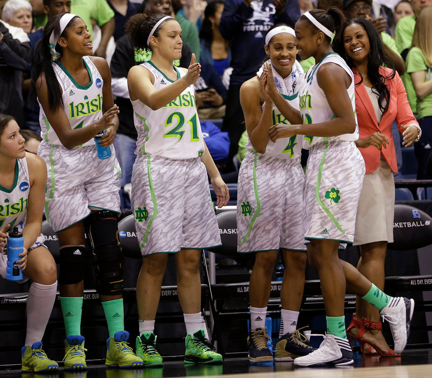 Description of . Notre Dame guard Jewell Loyd, right is welcomed to the bench by teammates Notre Dame guard Skylar Diggins, second from right,  Kayla McBride (21)  and Ariel Braker (44) during the second half of a regional semi-final of an NCAA college basketball tournament  Sunday, March 31,2013 in Norfolk, Va.  (AP Photo/Steve Helber)