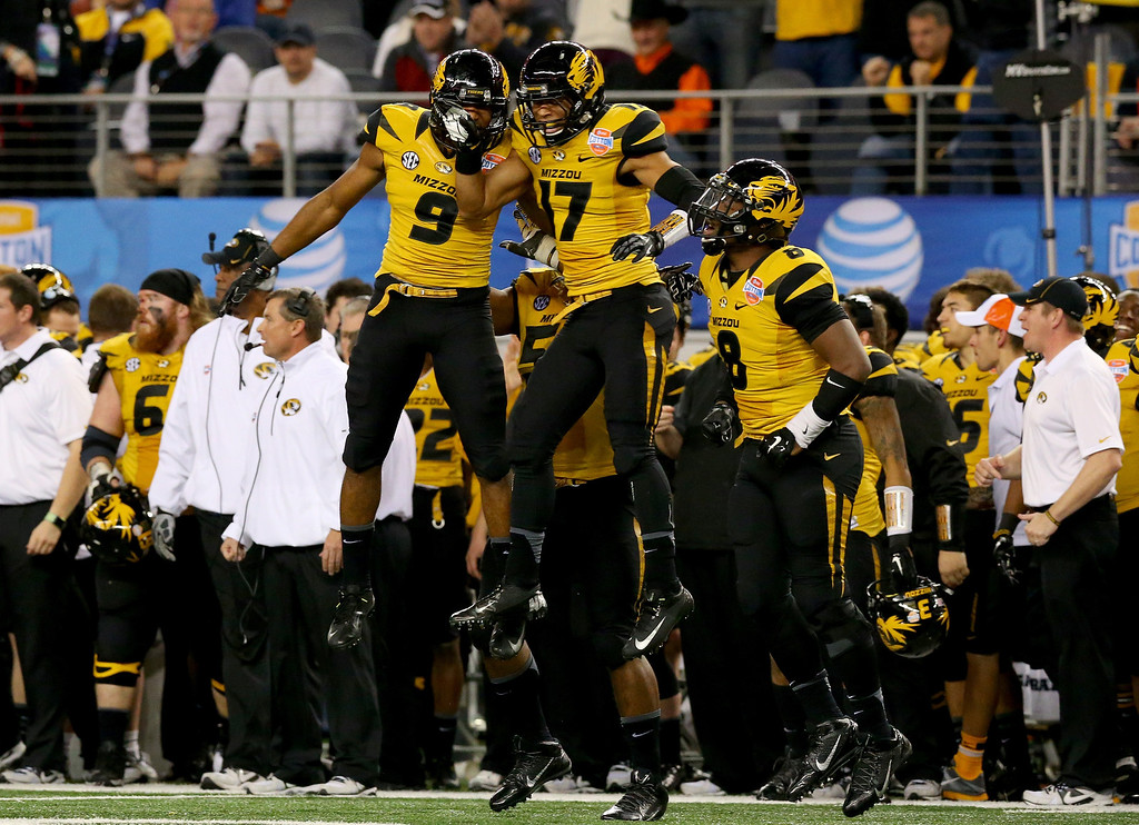 Description of . ARLINGTON, TX - JANUARY 03:  Braylon Webb #9 of the Missouri Tigers celebrates with teammate Matt White #17 after Webb intercepts a pass in the third quarter against the Oklahoma State Cowboys during the AT&T Cotton Bowl on January 3, 2014 in Arlington, Texas.  (Photo by Ronald Martinez/Getty Images)