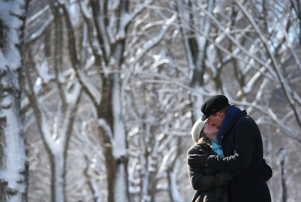 . NEW YORK, NY - FEBRUARY 09:  A couple kisses in a snow-covered Central Park on February 9, 2013 in New York City. The park received almost a foot of snow, as New York was spared the worst of the massive snow storm that hit the U.S. Northeast. (Photo by John Moore/Getty Images)