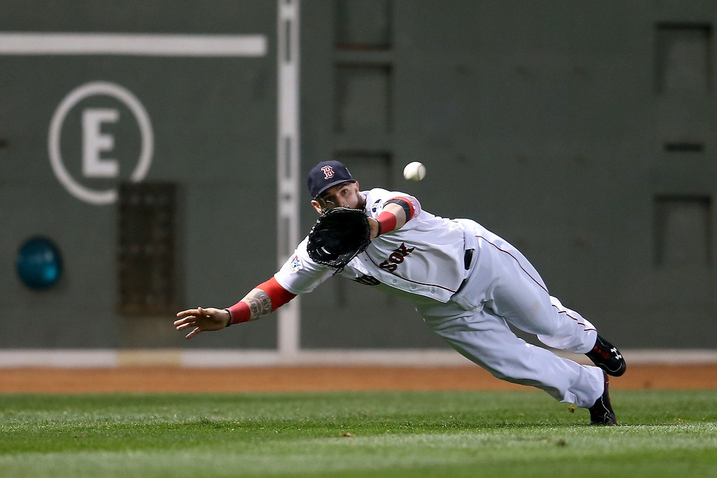 Description of . Jonny Gomes #5 of the Boston Red Sox catches a ball hit by Matt Adams #53 of the St. Louis Cardinals in the fifth inning of Game One of the 2013 World Series at Fenway Park on October 23, 2013 in Boston, Massachusetts.  (Photo by Rob Carr/Getty Images)