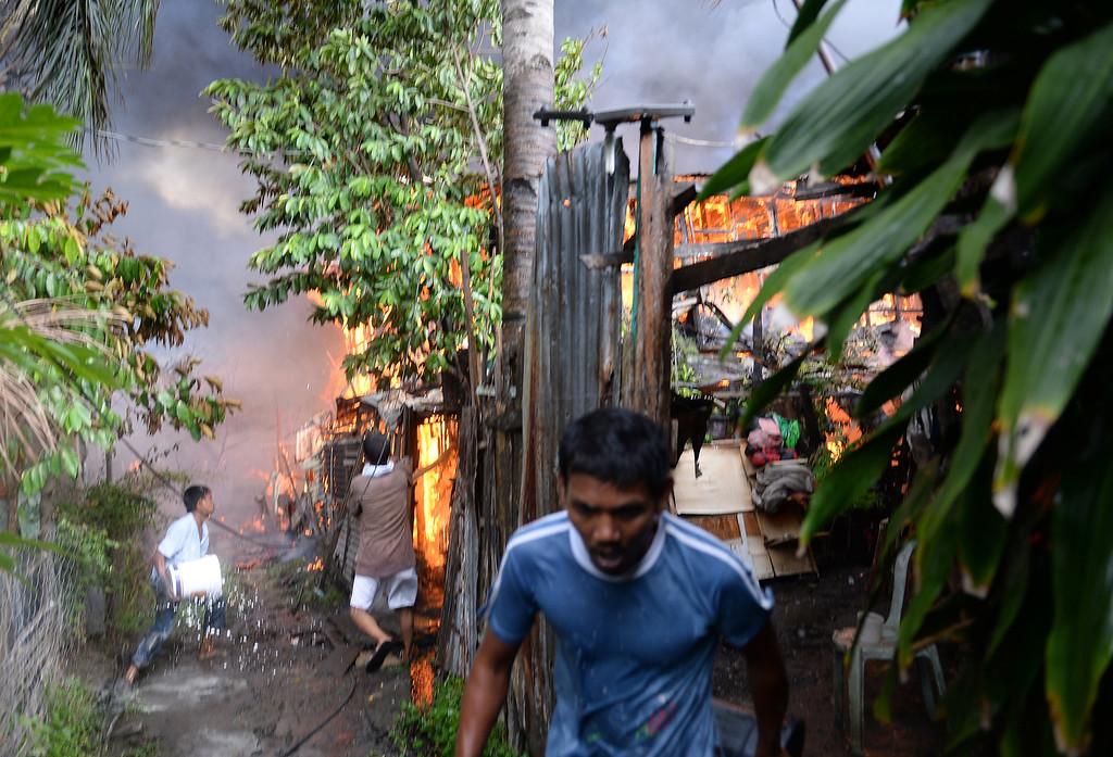 Description of . Residents try to put out fires in their homes during a fire fight between government troops and Muslim rebels in Zamboanga City, on the southern island of Mindanao on September 12, 2013.    AFP PHOTO/TED ALJIBE/AFP/Getty Images
